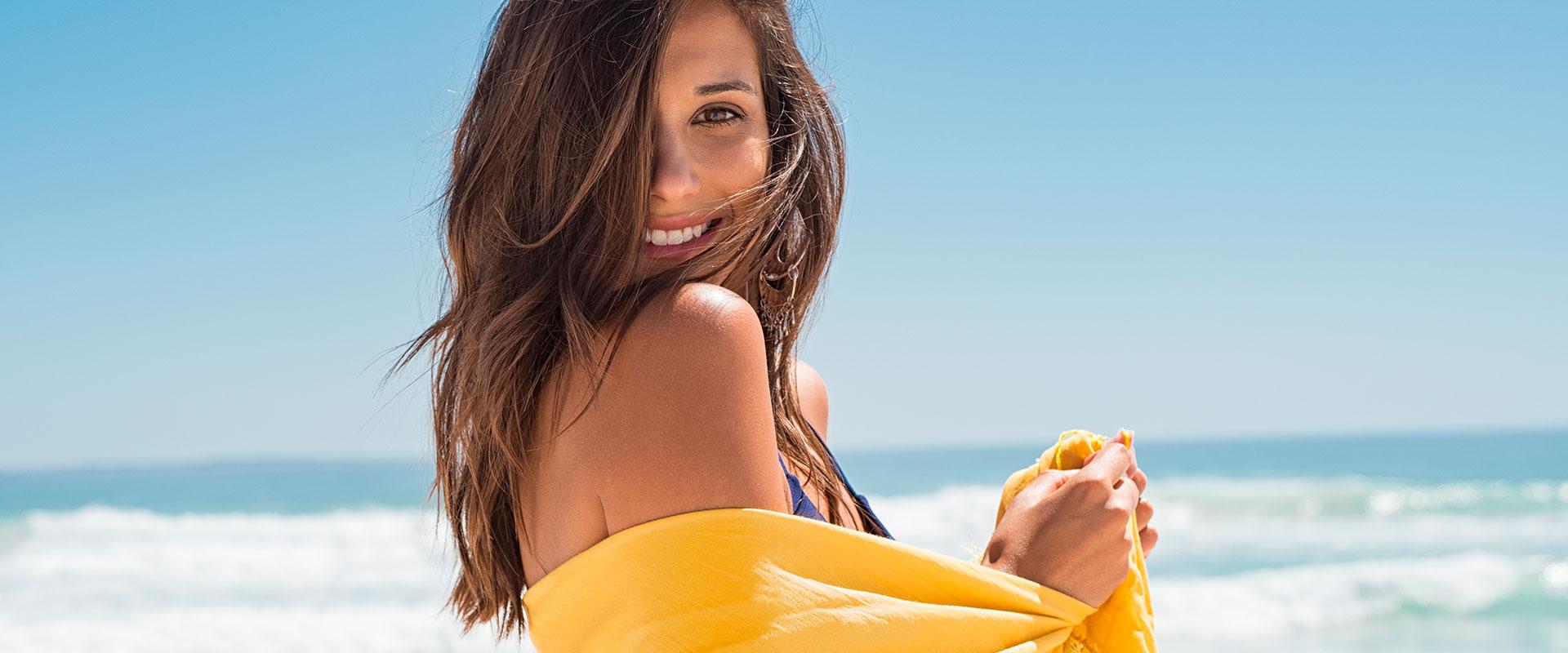 Mujer feliz con look de playa.