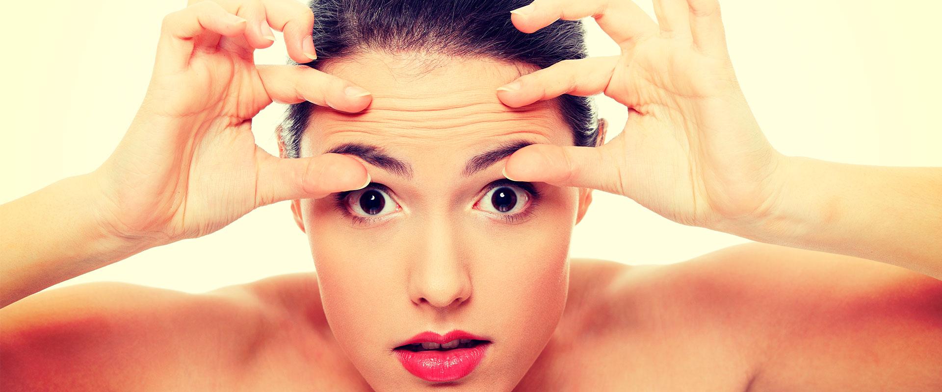 Mujer viéndose al espejo previniendo los signos de la edad con DermaWand.