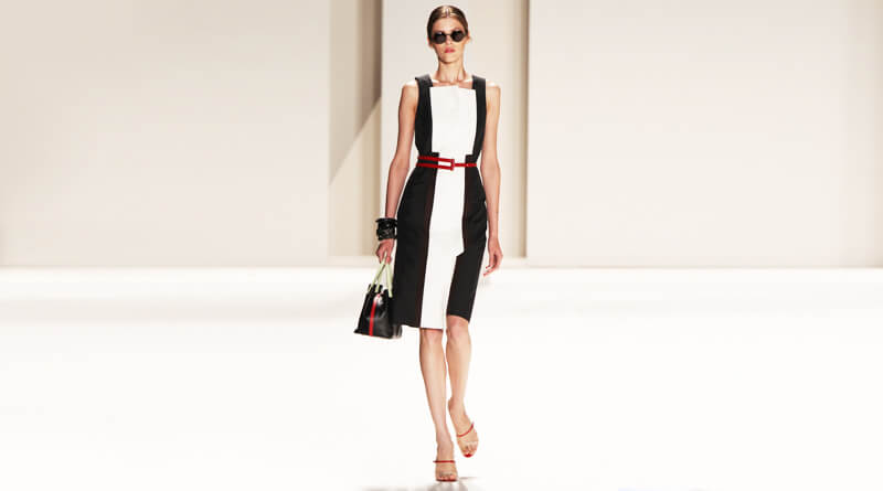 Imagen de mujer con figura estilizada, usando un vestido blanco con negro.