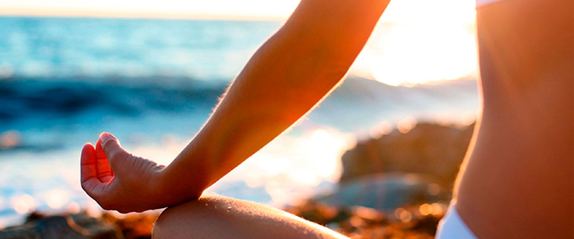 Mujer sentada en la playa en posición de flor de loto.