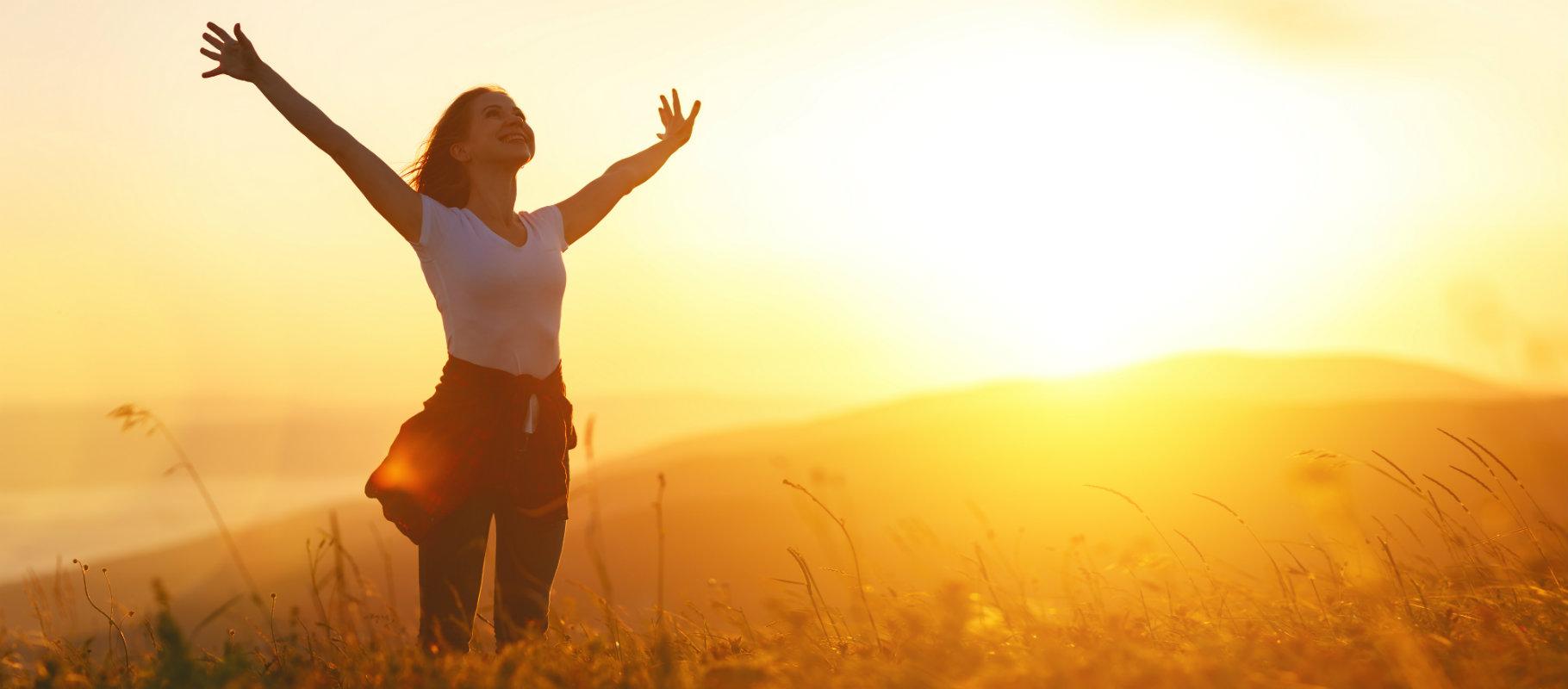 Mujer con los brazos extendidos en la pradera mientras amanece
