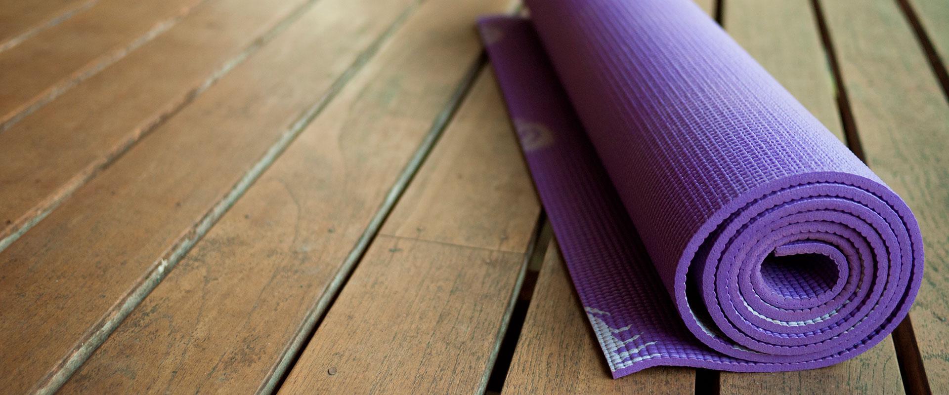 Tapete de yoga para la cintura, enrollado en el piso.