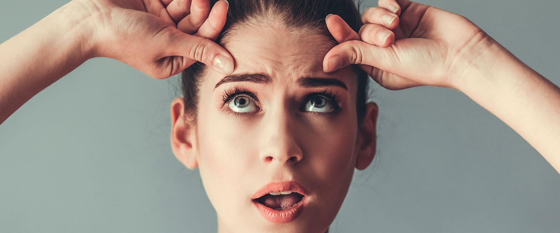 Mujer en sus treintas, estirando la piel de su rostro para evitar las arrugas.