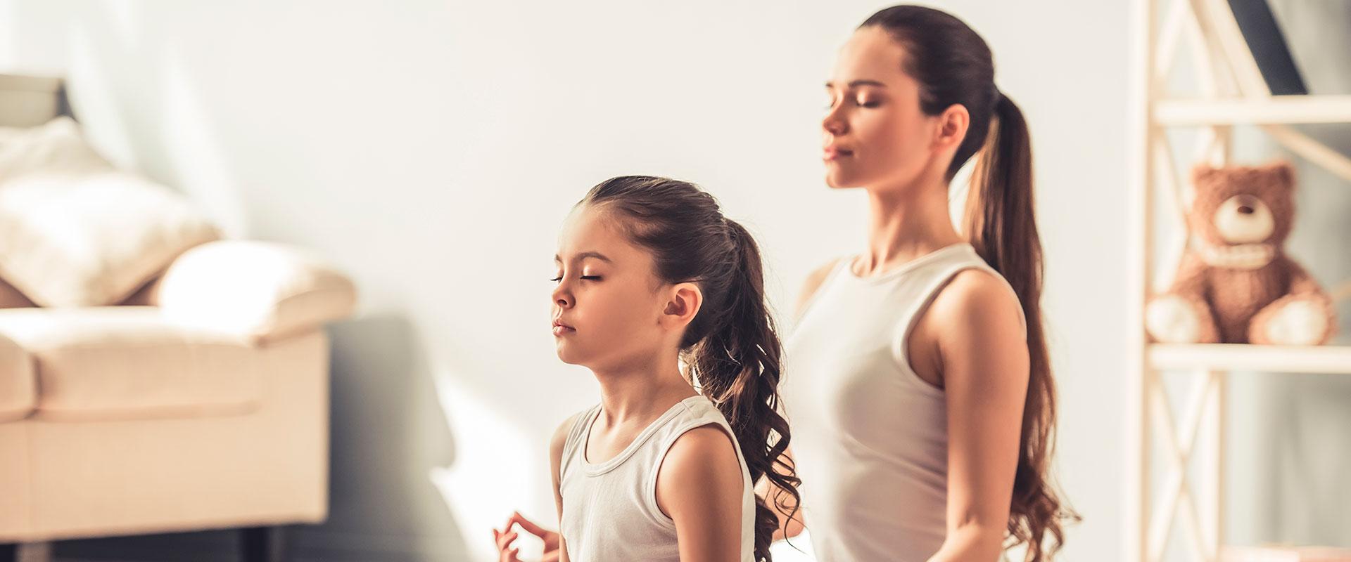 Madre e hija practicando yoga.