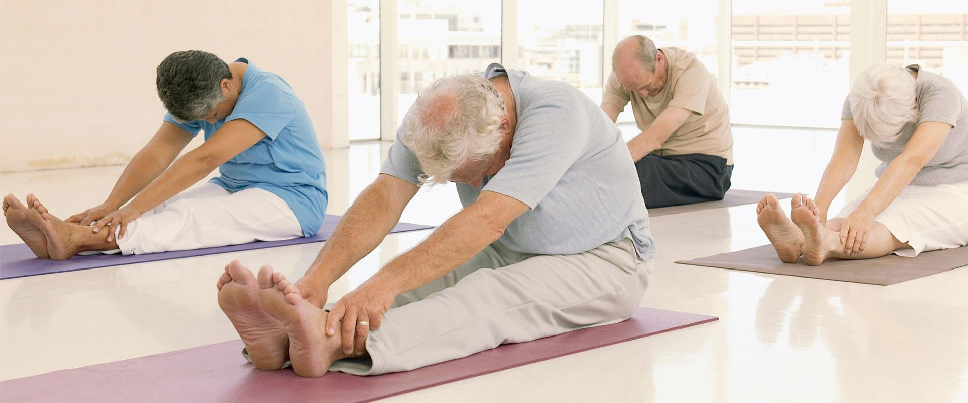 Adultos mayores haciendo pilates para tener una vida fitness.