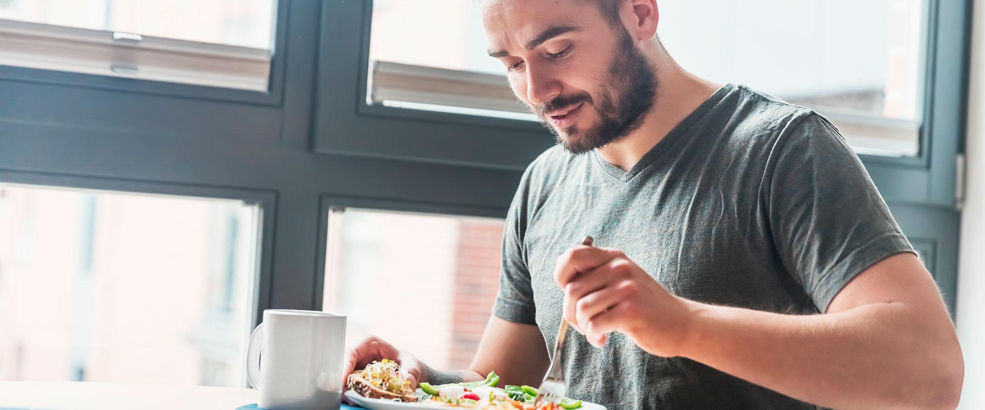 Hombre feliz comiendo ensalada.
