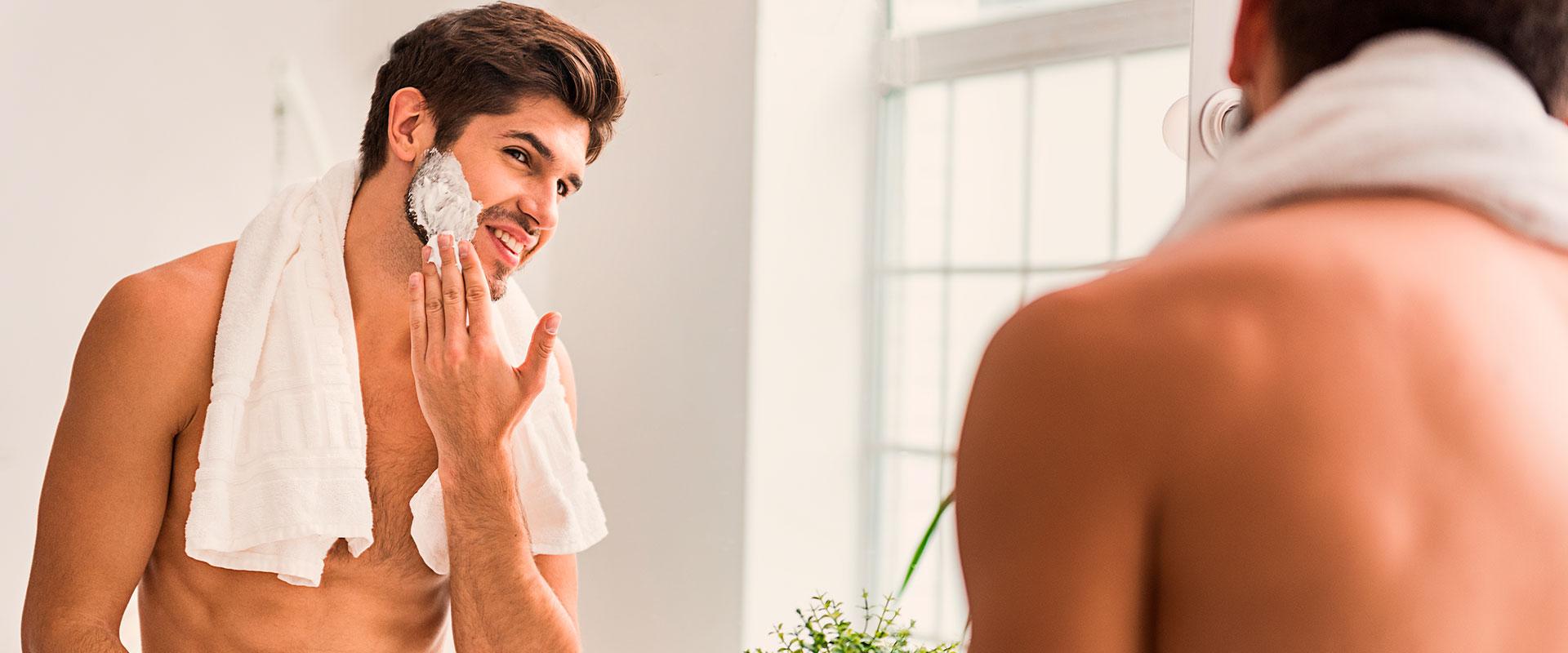 Hombre viéndose al espejo, poniéndose crema en el rostro para cuidar su piel durante el otoño.
