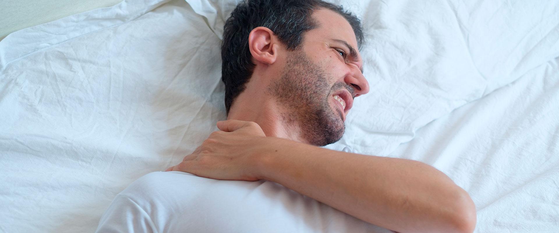 Hombre despertando con dolor de cuello debido a no dormir sobre una almohada soñare.