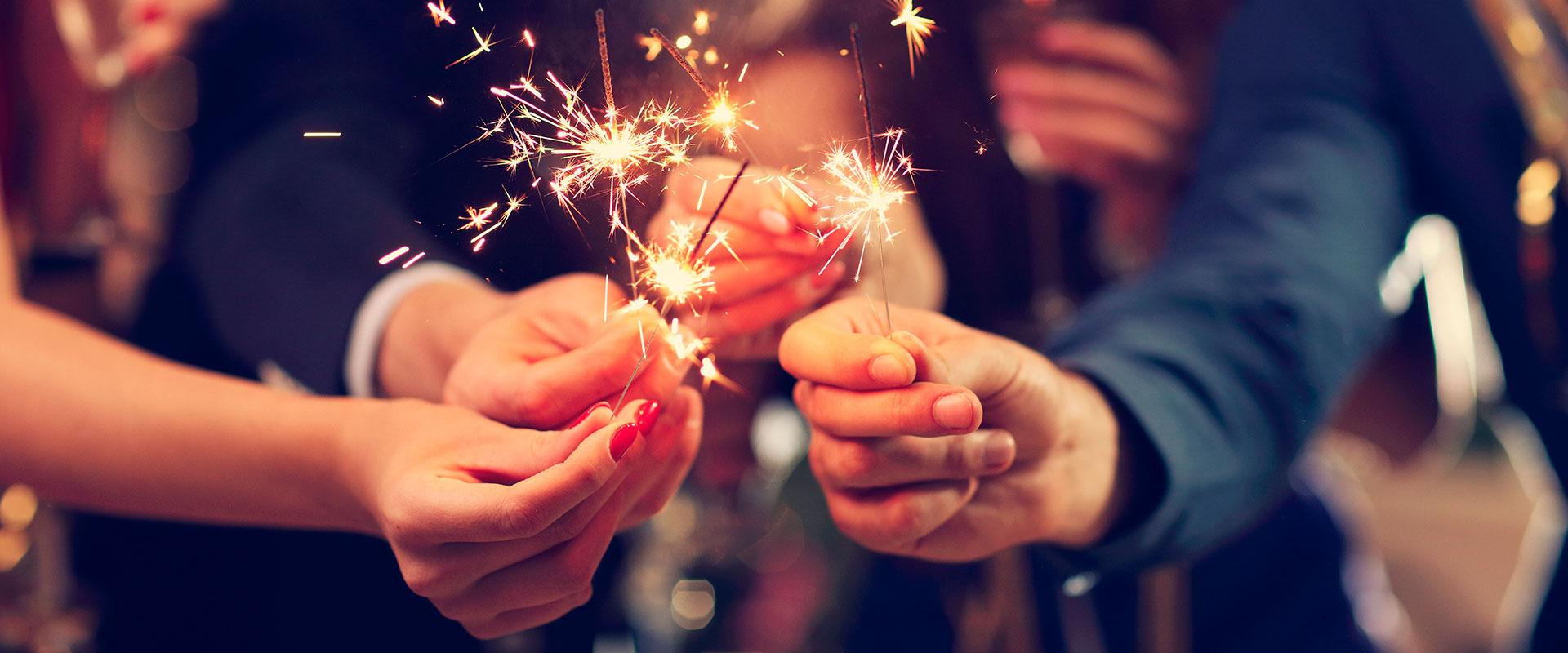 Personas festejando el 31 de diciembre con luces de bengala.