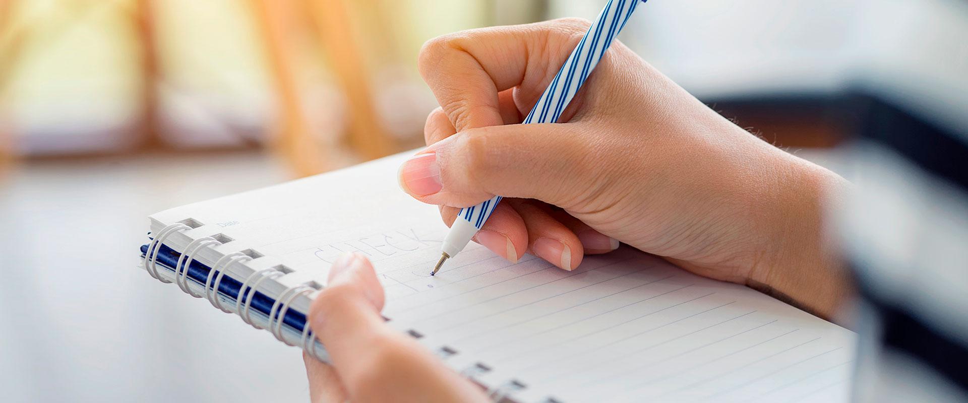 Persona escribiendo sus propósitos de año nuevo.