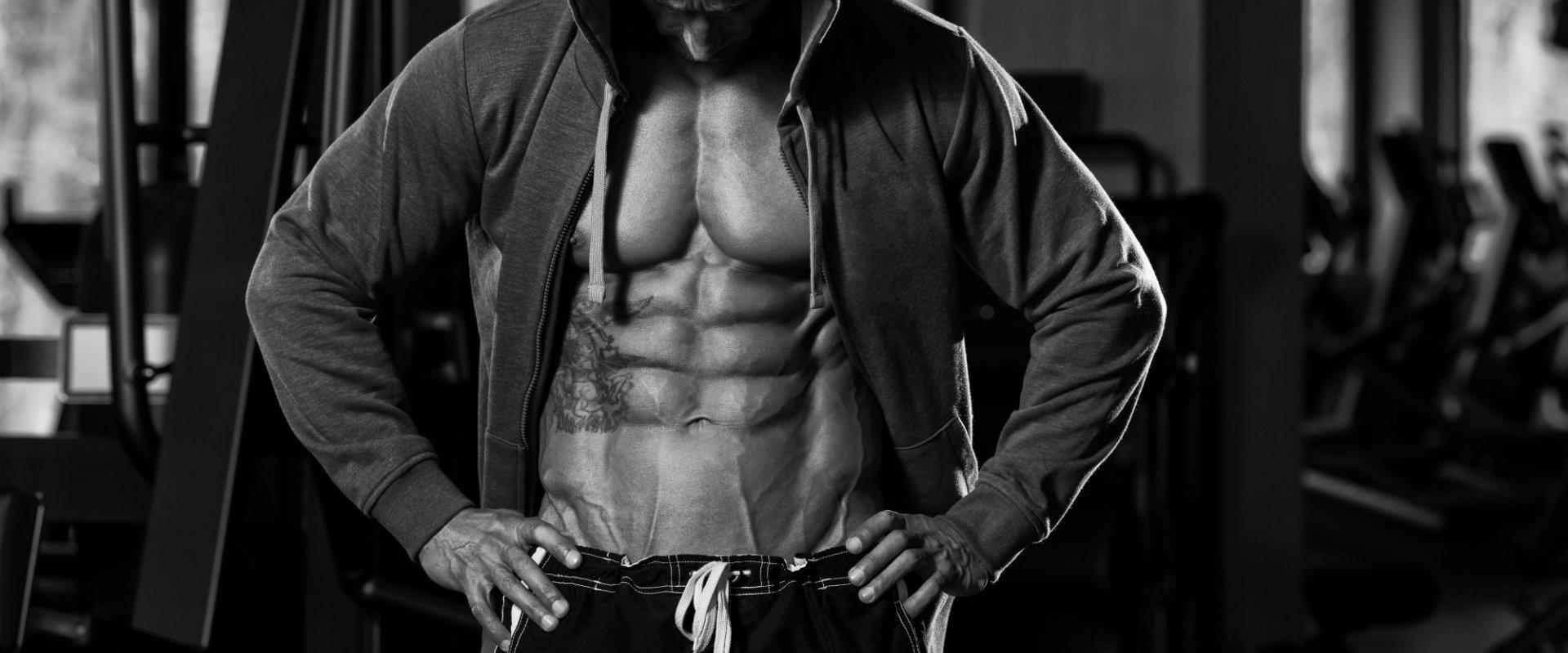 Imagen de hombre en blanco y negro mostrando su abdomen plano