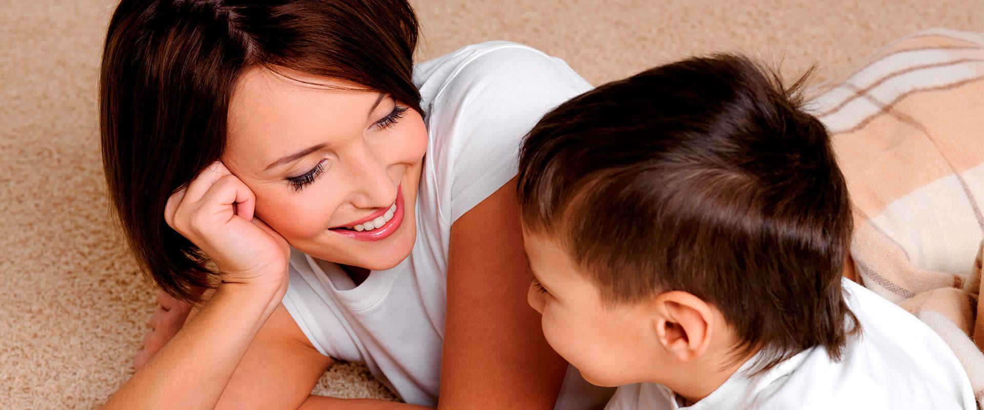 Mamá e hijo platicando alegremente sobre la alfombra.