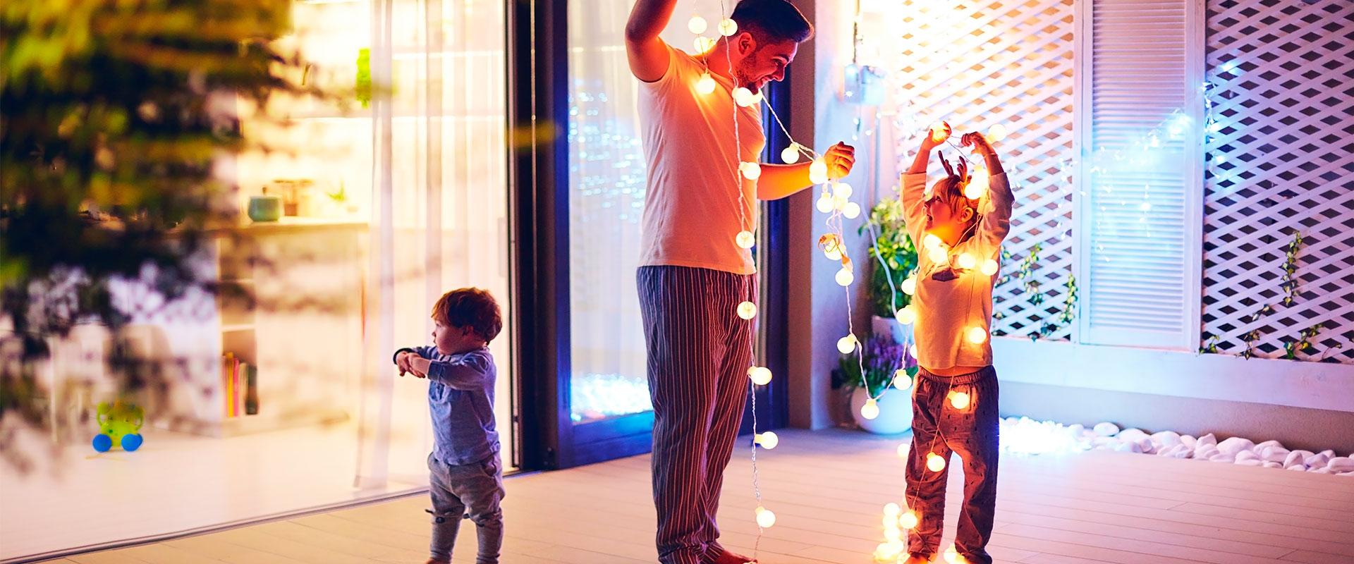 Padre e hijos adornando la casa con luces para una fiesta de Navidad.