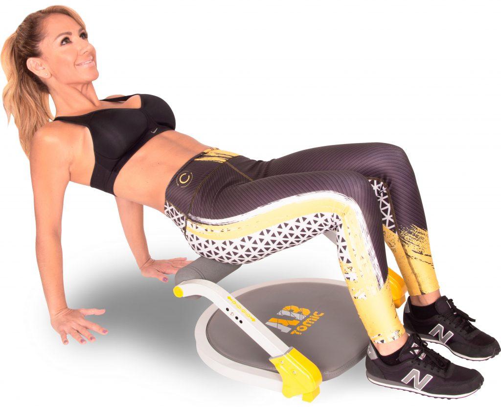 Mujer utilizando el aparato de ejercicio Ab Tomic, haciendo el ejercicio Puente.