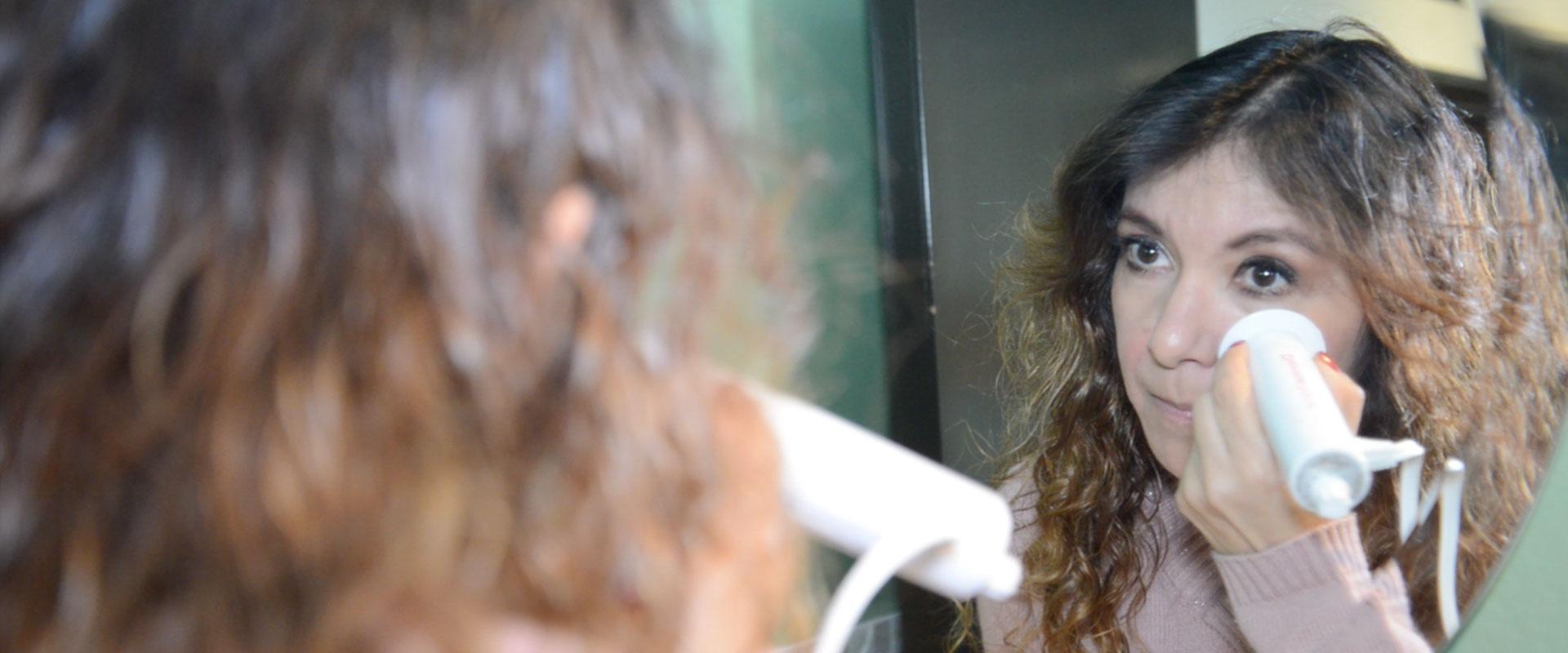 Mujer frente al espejo usando DermaWand.