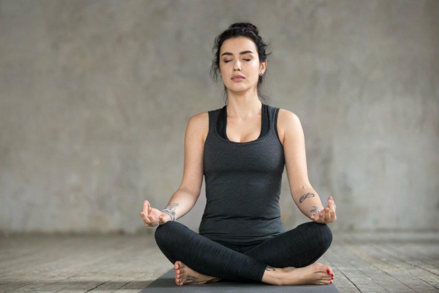 Mujer haciendo yoga postura de loto o padmasana