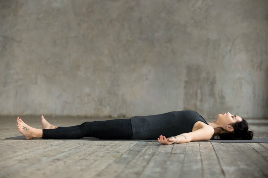 Mujer haciendo yoga postura del cadáver o savasana