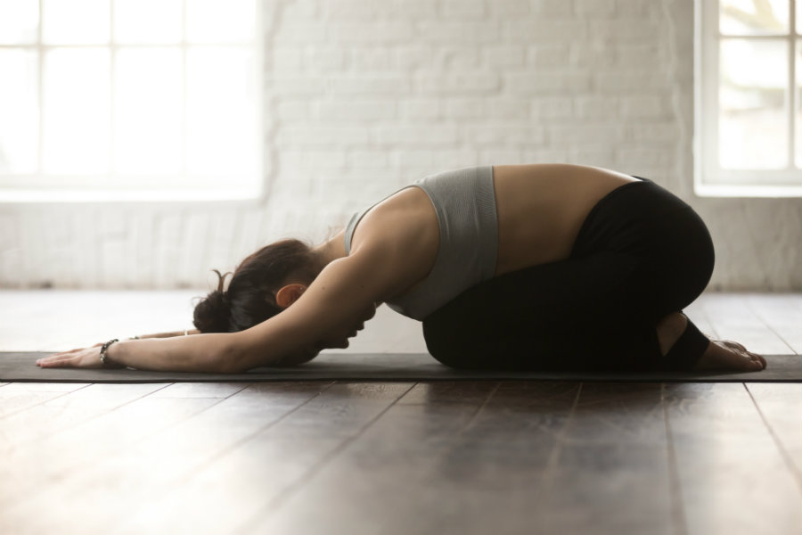Mujer haciendo yoga postura del niño o balasana