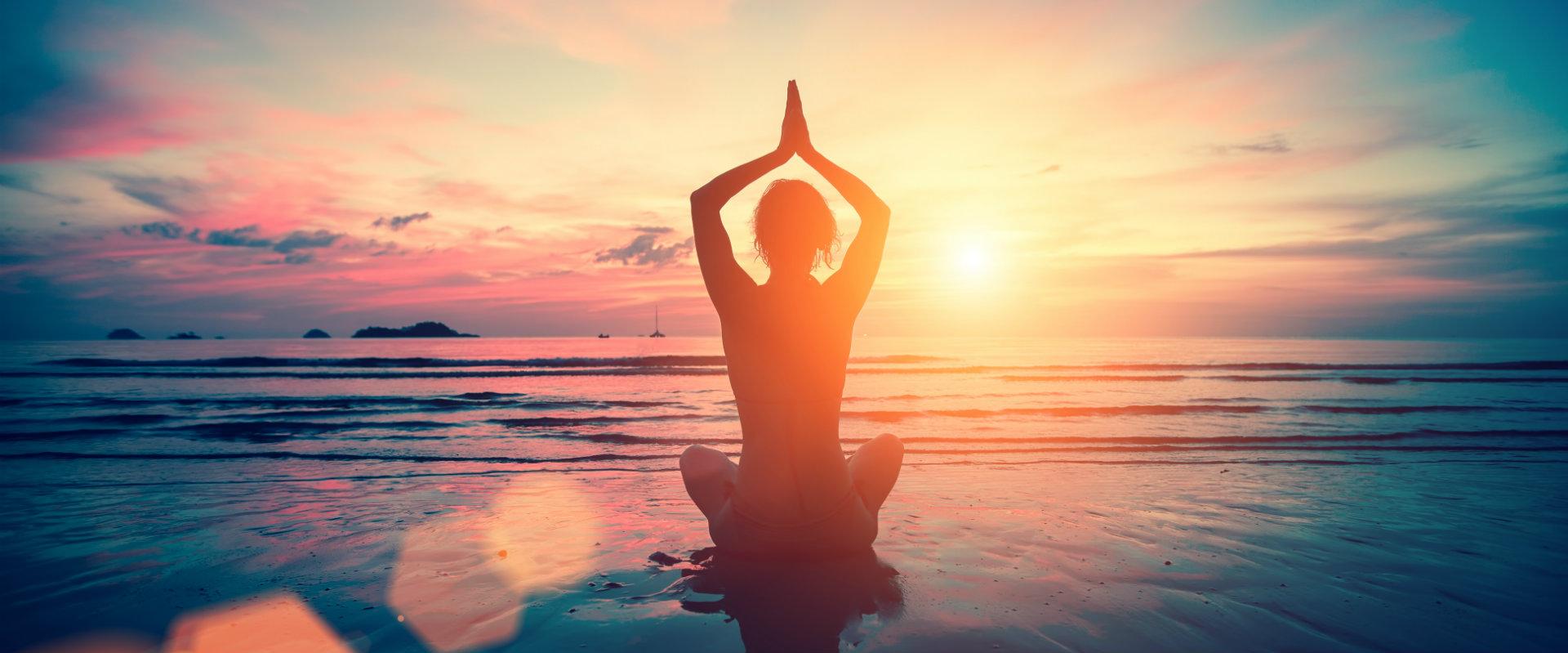 Mujer haciendo yoga al amanecer junto al mar