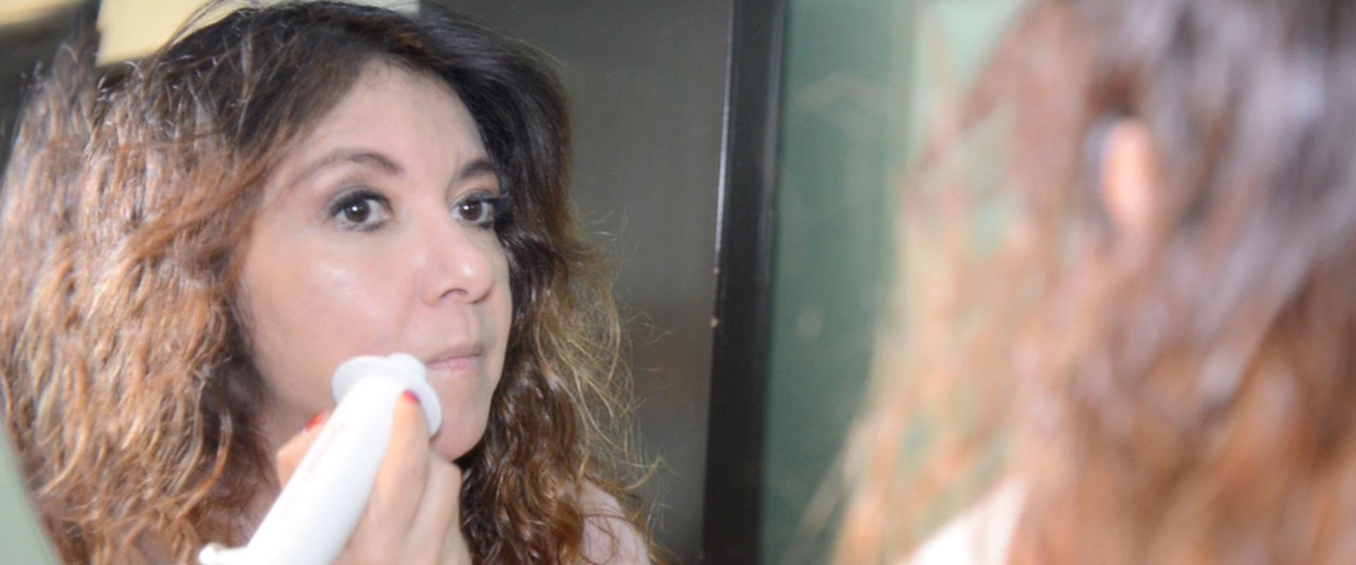 Mujer usando su DermaWand frente al espejo.