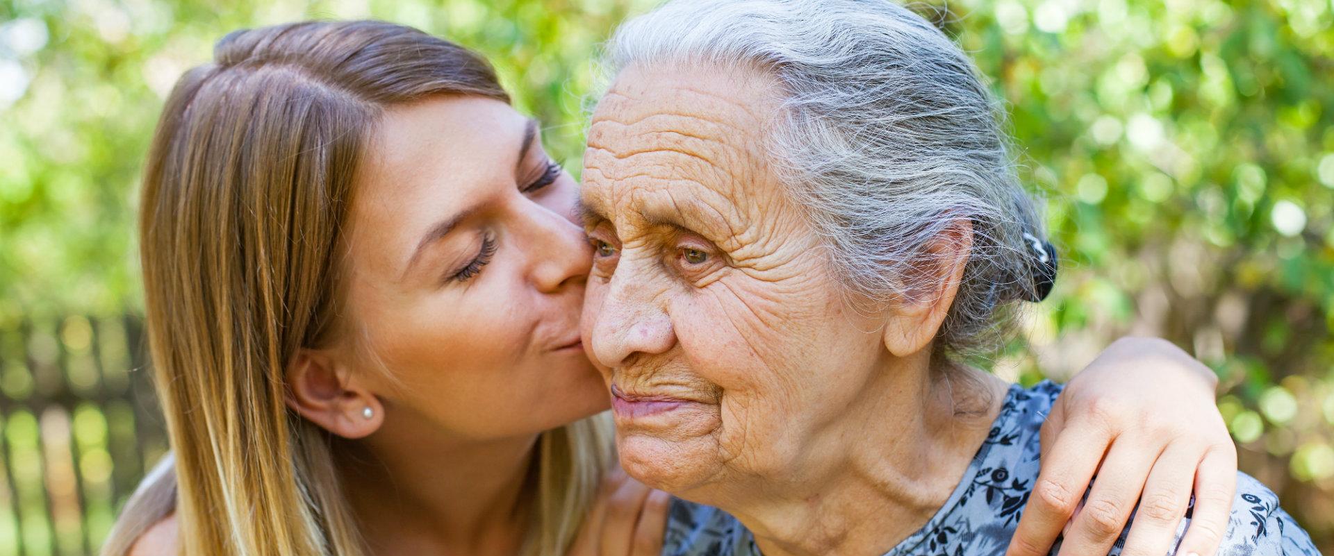 Mujer joven besando una mujer de la tercera edad o abuela
