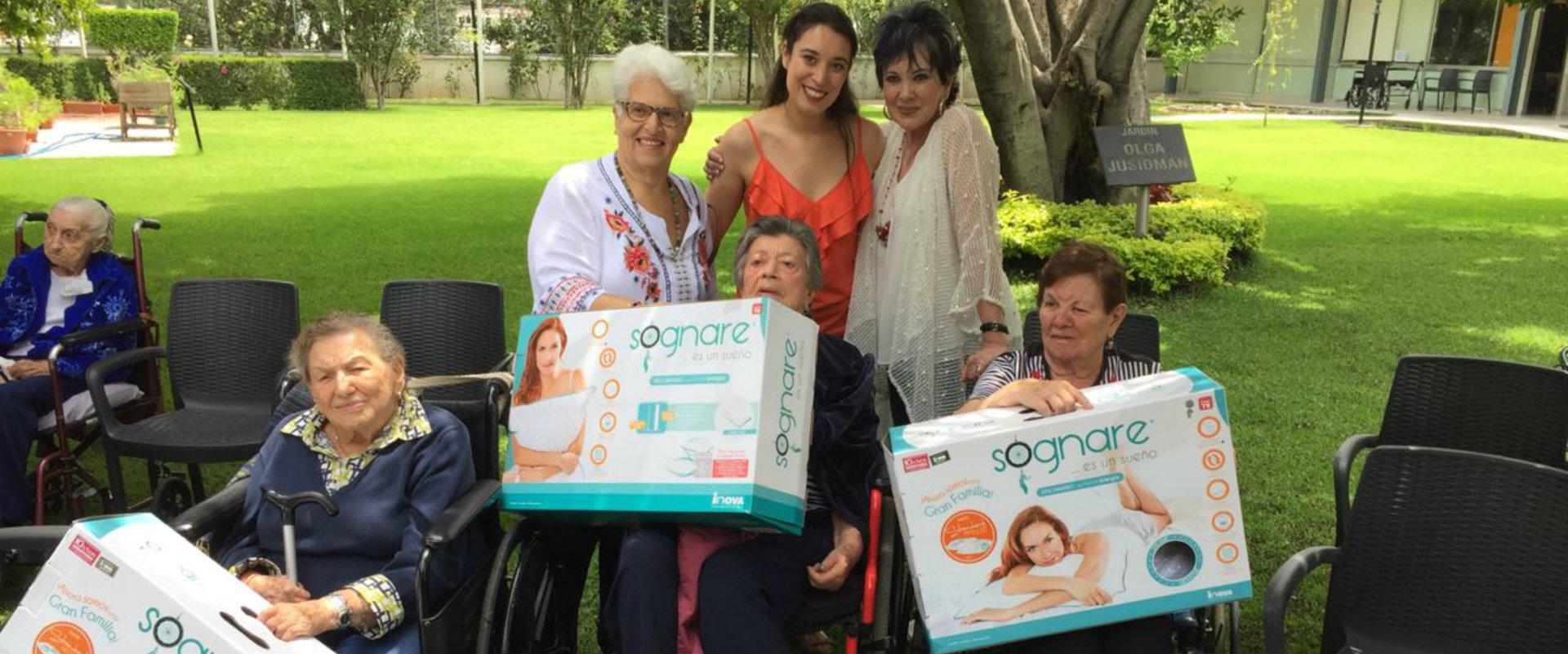 Representantes de Grupo Inova y Fundación Inova entregando almohadas sognare a adultos mayores