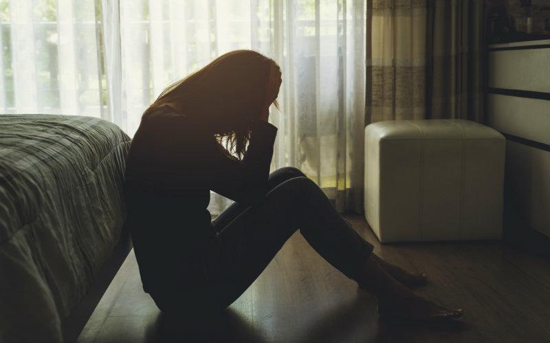 Mujer en su cuarto sentada en el piso de su cuarto
