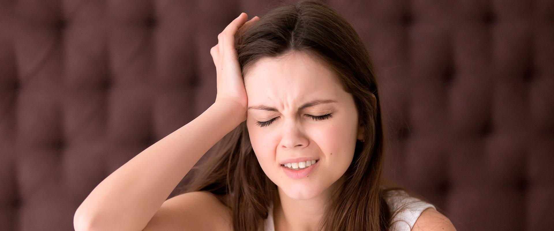 Mujer con dolor de cabeza por una resaca debido a la fiesta.