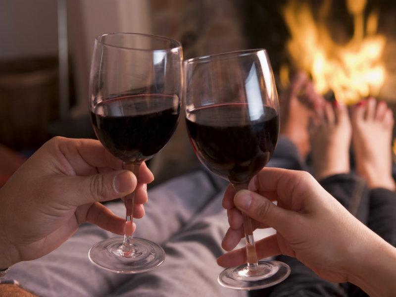 Una pareja juntos al fuego disfrutando una copa de vino