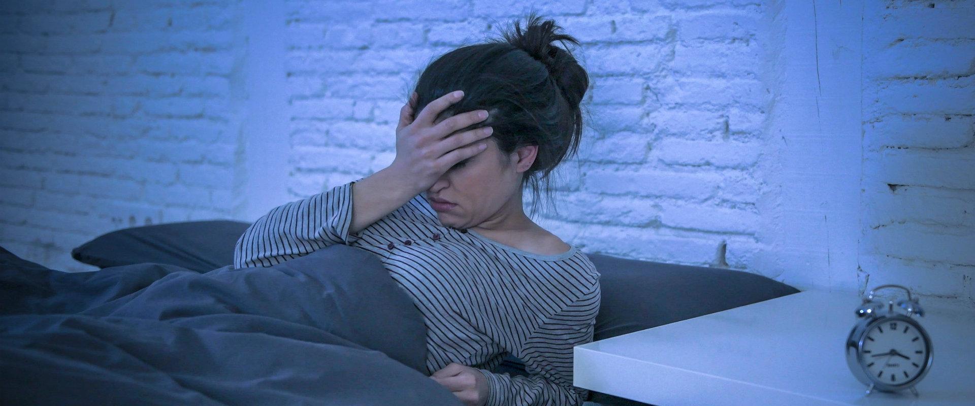 Mujer acostada en su cama sin poder dormir