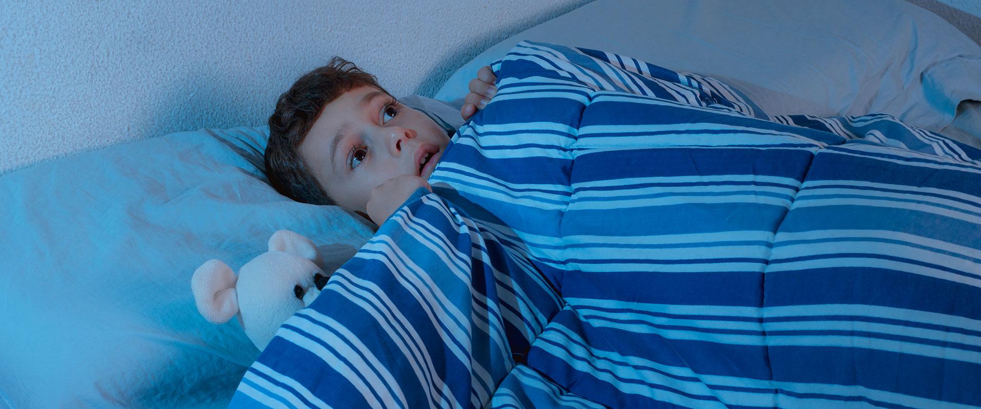 Niño despertando asustado a la mitad de la noche.