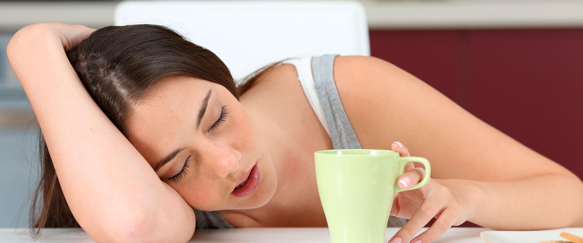 Mujer con narcolepsia durmiendo mientras toma café.