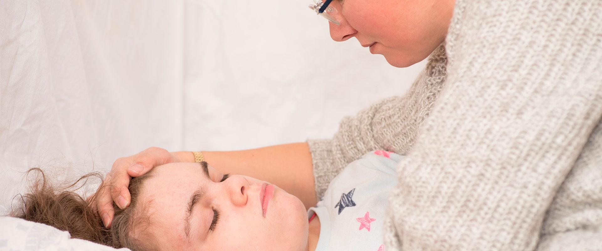 Mamá tranquilizando a su hija por un episodio de epilepsia nocturna.