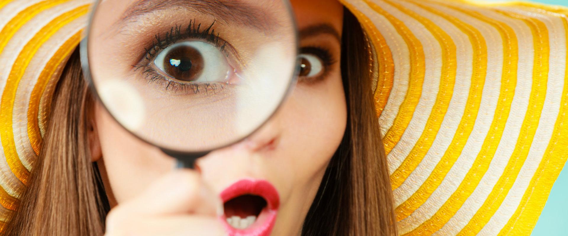 Mujer sostiene una lupa cerca de su ojo y se sorprende