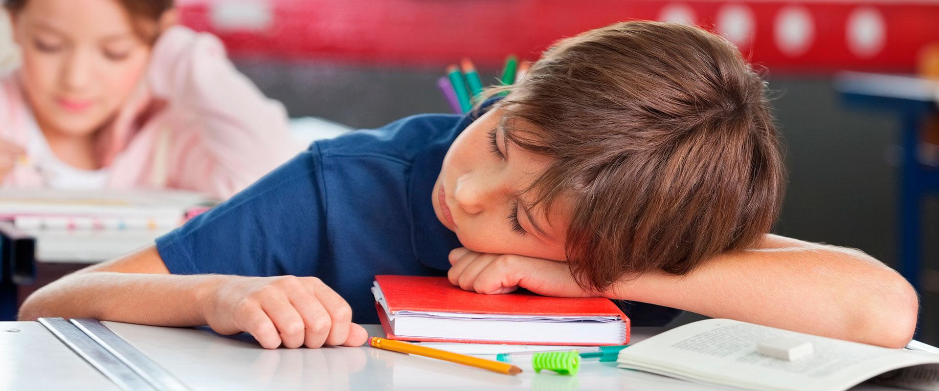 Niño durmiendo en clase por tener un trastorno del sueño.
