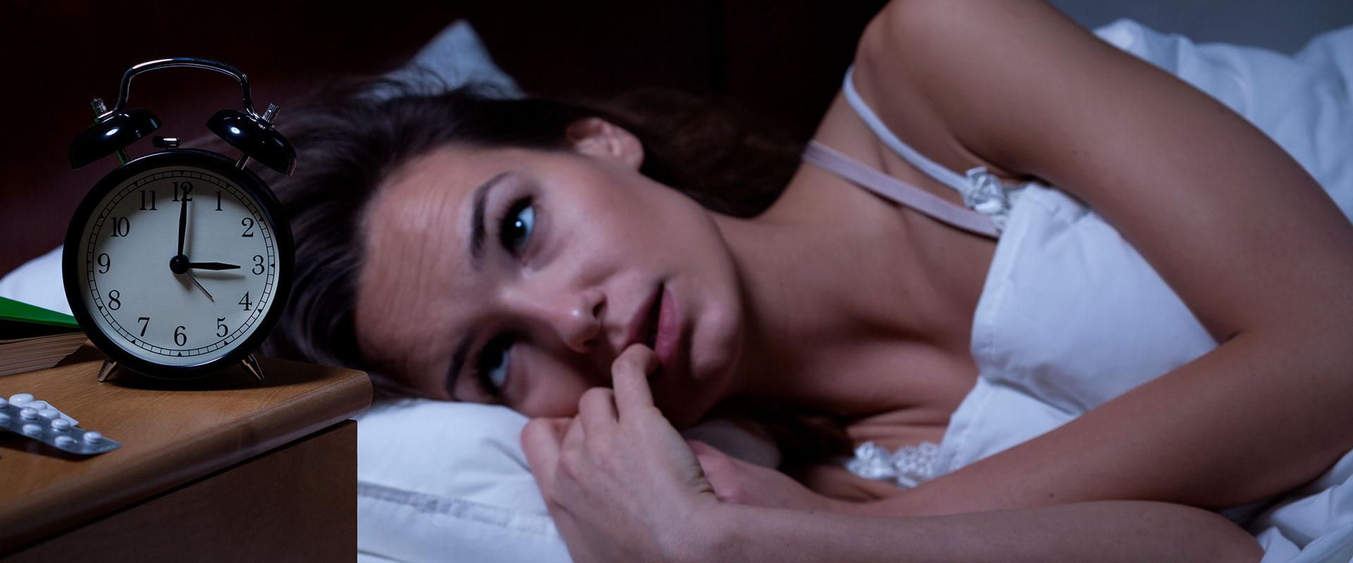 Mujer con insomnio por comer alimentos que no la dejan dormir mejor.