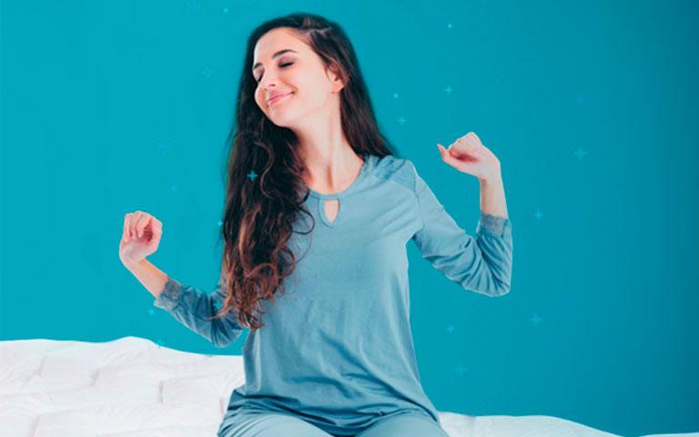 Mujer despertando en la mañana sobre su cubre colchón sognare