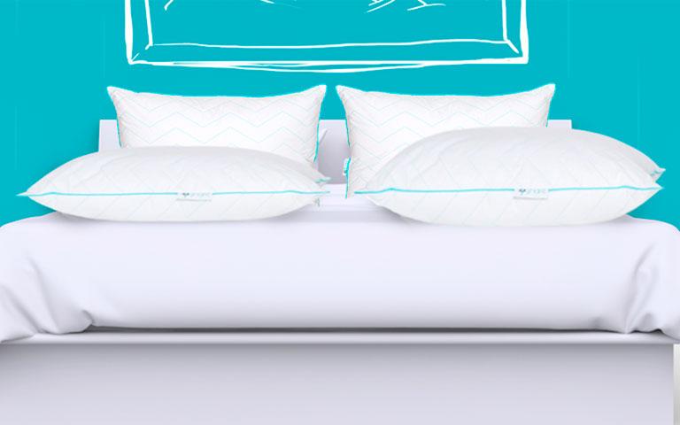 Diferentes tamaños de almohada soñare encima de una cama.