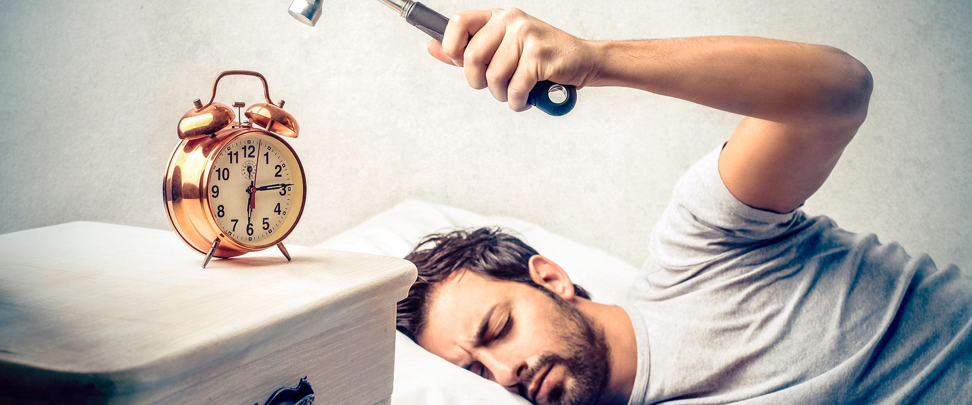 Hombre tratando de destruir su despertador.